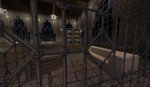 Quatre étagères de livres derrière une grille en fer.