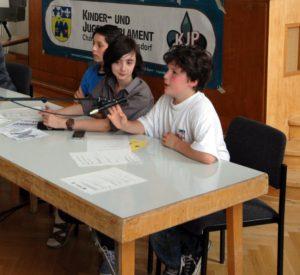 Un adolescent au micro dans un conseil d'enfant